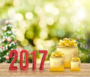 rotes Funkeln 2017 und goldenes Geschenk auf hölzerner Tabelle mit Weihnachten Stockbild