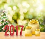 rotes Funkeln 2017 und goldenes Geschenk auf hölzerner Tabelle mit Weihnachten Stockfoto