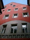Rotes Gebäude mit Fenstern stockbild