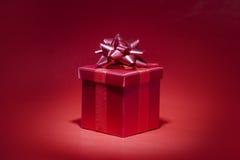 Rotes Geschenk auf rotem Hintergrund Stockbilder