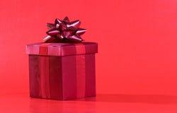 Rotes Geschenk auf rotem Hintergrund Lizenzfreie Stockfotos