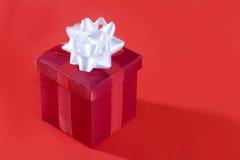 Rotes Geschenk auf rotem Hintergrund Stockbild