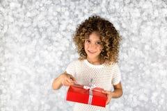 Rotes Geschenk Bild eines kleinen weißen kaukasischen Mädchens mit dem gelockten Haar, das rote Geschenkbox mit weißem Band gegen Lizenzfreies Stockfoto