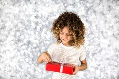 Rotes Geschenk Bild eines kleinen weißen kaukasischen Mädchens mit dem gelockten Haar, das rote Geschenkbox mit weißem Band gegen Stockbilder