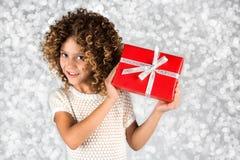 Rotes Geschenk Bild eines kleinen weißen kaukasischen Mädchens mit dem gelockten Haar, das rote Geschenkbox mit weißem Band gegen Stockfoto