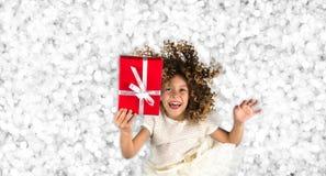 Rotes Geschenk Bild eines kleinen weißen kaukasischen Mädchens mit dem gelockten Haar, das rote Geschenkbox mit weißem Band gegen Lizenzfreies Stockbild