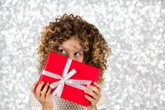 Rotes Geschenk Bild eines kleinen weißen kaukasischen Mädchens mit dem gelockten Haar, das rote Geschenkbox mit weißem Band gegen Stockbild