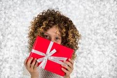 Rotes Geschenk Bild eines kleinen weißen kaukasischen Mädchens mit dem gelockten Haar, das rote Geschenkbox mit weißem Band gegen Lizenzfreie Stockbilder