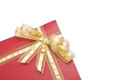Rotes Geschenk mit einem goldenen Bogen Stockfotos