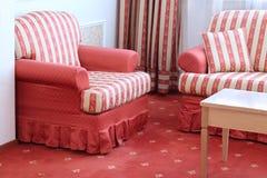 Rotes gestreiftes Sofa mit Kissen und Lehnsessel Stockbilder