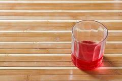 Rotes Getränk auf Bambusboden Stockbild