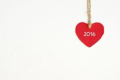Rotes Gewebeherz mit dem Wort 2016, das an der Wäscheleine hängt Stockfoto
