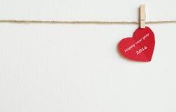 Rotes Gewebeherz mit dem Wort des guten Rutsch ins Neue Jahr 2016, das am Cl hängt Stockfoto