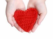 Rotes gewirktes Herz in den Händen stockfotografie