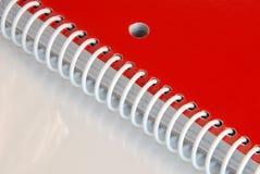 Rotes gewundenes Notizbuch Stockbild