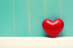 Rotes glänzendes Herz auf Weinleseknickentenholz lizenzfreie stockbilder