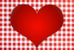 Rotes glänzendes Herz gegen roten und weißen karierten Hintergrund Lizenzfreie Stockfotografie