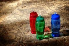 Rotes, grünes, blaues Wasser-Flaschen auf rauen Felsen Stockfotografie