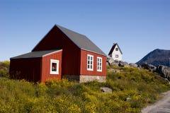Rotes Häuschen in Grönland mit weißer Kirche Lizenzfreie Stockfotografie