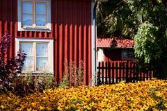 Rotes Häuschen mit Blume draußen. Lizenzfreies Stockbild