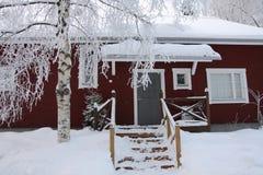 Rotes hölzernes finnisches Haus im Winter Stockbild
