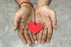 Rotes hölzernes Herz in den schmutzigen Händen lizenzfreies stockfoto