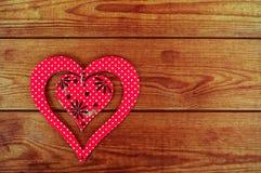 Rotes hölzernes Herz gesetzt auf ein braunes hölzernes Brett Stockbilder