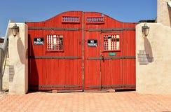 Rotes hölzernes Tor in einer Lehmziegelmauer Lizenzfreies Stockfoto