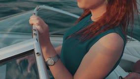 Rotes Haarmädchen im Türkiskleider-Antriebsmotorboot Stellung hinter zwei Kiefern unterhaltung stock video footage