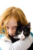 Rotes Hauptmädchen, das ein schwarzes weißes Kätzchen anhält Stockfotos