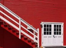 Rotes Haus außen mit weißen Türen und Treppen Stockbild