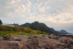 Rotes Haus auf dem Ufer mit Ansicht zum Berg und zum Sonnenuntergang auf dem Meer im Norwegen am Sommer lizenzfreie stockbilder
