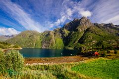 Rotes Haus auf dem Ufer von See mit Ansicht zu den Bergen im Norwegen am Sommer Stockfoto