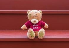 Rotes Hemd der braunen Abnutzung des TEDDYBÄREN Farbmit der Liebe, die auf rotem s sitzt Stockbild