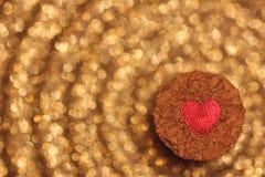 Rotes Herz auf dem Pfropfen mit goldenem bokeh Hintergrund Stockfoto