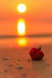Rotes Herz auf dem Strand bei Sonnenuntergang Lizenzfreies Stockfoto