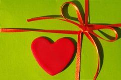 Rotes Herz auf einem grünen Hintergrund mit einer Bürokratie und einem Bogen Stockbilder
