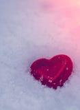 Rotes Herz auf einem Hintergrund des Schnees bei Sonnenuntergang Valentinsgruß `s Tag Lizenzfreie Stockbilder