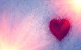 Rotes Herz auf einem Hintergrund des Schnees bei Sonnenuntergang Valentinsgruß `s Tag Stockbild