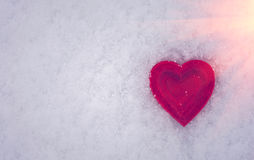 Rotes Herz auf einem Hintergrund des Schnees bei Sonnenuntergang Valentinsgruß `s Tag Stockfotografie