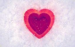 Rotes Herz auf einem Hintergrund des Schnees Valentinsgruß `s Tag Stockfotografie