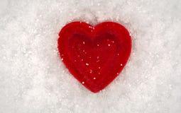 Rotes Herz auf einem Hintergrund des Schnees Valentinsgruß `s Tag Lizenzfreies Stockfoto