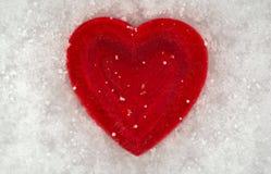 Rotes Herz auf einem Hintergrund des Schnees Valentinsgruß `s Tag Lizenzfreie Stockbilder