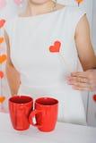 Rotes Herz auf einem Stock in einer weiblichen Hand auf einem weißen Kleid nahe bei zwei roten Schalen Lizenzfreie Stockbilder