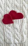 Rotes Herz auf einem Weiß strickte Hintergrund, gestrickte Beschaffenheit Stockfotografie