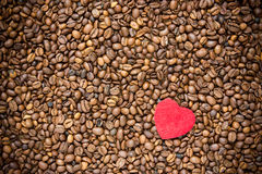 Rotes Herz auf Kaffeebohnehintergrund stockfotografie