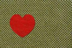 Rotes Herz auf olivgrünem Gewebe, am 23. Februar Stockbild