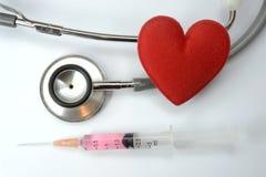 Rotes Herz auf Stethoskop und einer Spritze Lizenzfreie Stockfotografie