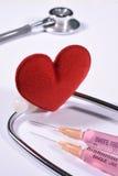 Rotes Herz auf Stethoskop und Spritze Stockfotos
