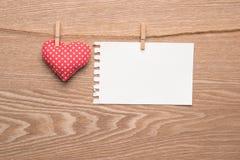 Rotes Herz, das über hölzernem Hintergrund mit Papier hängt lizenzfreie stockfotos